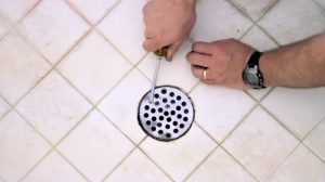 Opening a shower drain to unclog
